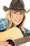 Cowgirl con la chitarra nel sorriso blu di fine della camicia Fotografia Stock Libera da Diritti