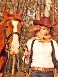 Cowgirl corriente con su caballo rojo. Foto de archivo