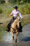 Cowgirl Crossing Pond. On palomino horse - splashing water stock photos
