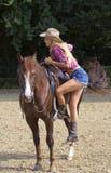 Cowgirl, das auf Pferd klettert Stockfoto