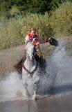 Cowgirl, das durch Teich galoppiert Lizenzfreies Stockfoto