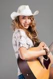 Cowgirl di Sesy in cappello di cowboy con la chitarra acustica Immagini Stock Libere da Diritti