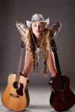 Cowgirl di Sesy in cappello di cowboy con la chitarra acustica Fotografie Stock Libere da Diritti