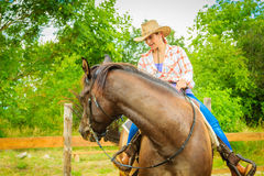 Cowgirl doing horse riding on countryside meadow Royalty Free Stock Photography