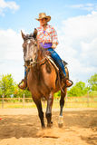 Cowgirl doing horse riding on countryside meadow. Taking care of animals, horsemanship, western competitions concept. Cowgirl doing horse riding on countryside royalty free stock image