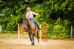 Cowgirl doing horse riding on countryside meadow. Taking care of animals, horsemanship, western competitions concept. Cowgirl doing horse riding on countryside stock photos
