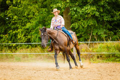Cowgirl doing horse riding on countryside meadow Stock Image