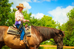 Cowgirl doing horse riding on countryside meadow Royalty Free Stock Photo