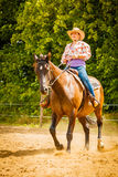 Cowgirl doing horse riding on countryside meadow. Taking care of animals, horsemanship, western competitions concept. Cowgirl doing horse riding on countryside Royalty Free Stock Photo