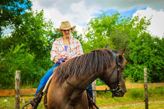 Cowgirl doing horse riding on countryside meadow. Taking care of animals, horsemanship, western competitions concept. Cowgirl doing horse riding on countryside stock photo