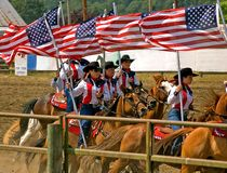 Cowgirl Drill Team on Horseback. This cowgirl drill team on horses are carrying the American flag by women participants on 7/4/09 at the 75th annual Loggerrodeo Royalty Free Stock Photos