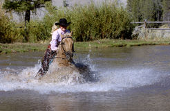 Cowgirl Galloping Horse into Pond. Cowgirl galloping into pond on palomino horse royalty free stock image