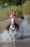 Cowgirl Galloping Through Pond. Cowgirl galloping grey horse through pond -- splashing water royalty free stock photo