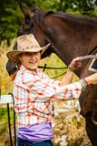 Cowgirl getting horse ready for ride on countryside royalty free stock image