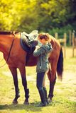 Cowgirl getting horse ready for ride on countryside. Taking care of animals, horsemanship, equine concept. Cowgirl getting horse ready for ride on countryside stock photography