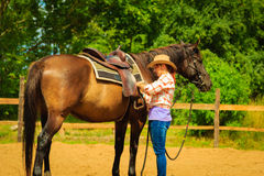 Cowgirl getting horse ready for ride on countryside Stock Photography
