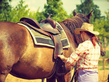 Cowgirl getting horse ready for ride on countryside Royalty Free Stock Photos