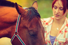 Cowgirl getting horse ready for ride on countryside. Taking care of animals, horsemanship, equine concept. Redhead cowgirl getting horse ready for ride on stock image