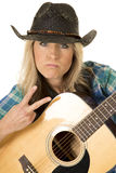 Cowgirl with guitar in blue shirt close peace sign Stock Photography