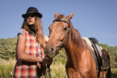 Cowgirl in hat with bay horse Royalty Free Stock Photos