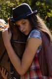 Cowgirl in hat with bay horse Stock Photos