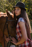 Cowgirl in hat with bay horse Royalty Free Stock Images