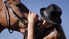 Cowgirl in hat with bay horse Royalty Free Stock Image