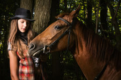 Cowgirl in hat with bay horse Stock Images