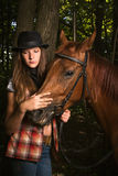 Cowgirl in hat with bay horse Stock Photography