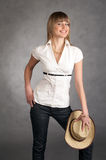 Cowgirl with a hat on a grey background Stock Images