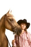 Cowgirl in hat holding her horse by bridle Royalty Free Stock Photo