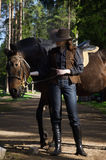 Cowgirl in hat hugging her horse Stock Photo
