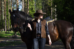 Cowgirl in hat hugging her horse Royalty Free Stock Photos