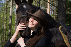Cowgirl in hat hugging her horse Stock Image