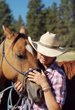 Cowgirl and Her Horse. Nice cowgirl giving her horse some attention stock image