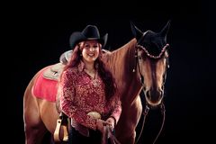 Cowgirl With Her Horse. Studio shot on black background Royalty Free Stock Photos