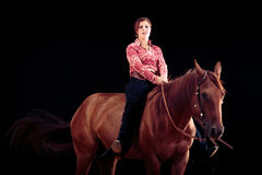 Cowgirl With Her Horse. Studio shot on black background Royalty Free Stock Image