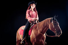 Cowgirl With Her Horse. Studio shot on black background Stock Photo