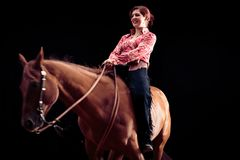 Cowgirl With Her Horse. Studio shot on black background Royalty Free Stock Photo