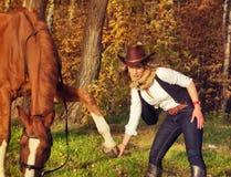 Cowgirl hermoso con su caballo rojo Fotografía de archivo