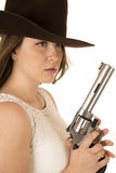 Cowgirl holding a big revolver with a dazed expression Royalty Free Stock Photos