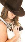 Cowgirl holding a larger revolver looking down Royalty Free Stock Photo