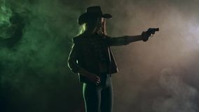 Cowgirl holds a revolver in her hands and aiming at the villain. Black smoke background. Slow motion. Side view. Cowgirl holds a revolver in her hands and stock video footage
