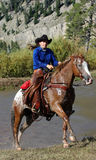 Cowgirl & Horse Emerging from Pond. Cowgirl on pinto horse exiting pond royalty free stock photography
