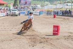 Cowgirl and horse gallop around second barrel at barrel racing event. WILLIAMS LAKE, BRITISH COLUMBIA, CANADA - JULY 2, 2016:  cowgirl and horse come around the Royalty Free Stock Images
