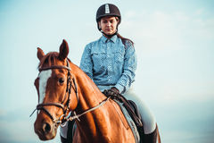 Cowgirl and horse. Cowgirl in a hat standing near a horse in a field Stock Image