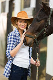 Cowgirl with horse. Pretty cowgirl with her horse in stable Stock Photography