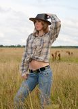 Cowgirl in jeans and a cowboy hat. Cowgirl in jeans and a cowboy hat at nature Royalty Free Stock Image