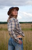 Cowgirl in jeans and a cowboy hat at nature Royalty Free Stock Photos