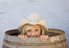 Cowgirl joven que sonríe por dentro de un barril Fotos de archivo libres de regalías